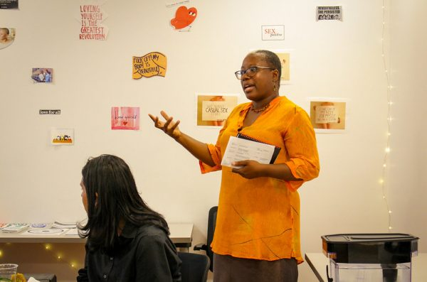 Director of WLRC, Natalie Bennet, stands and adresses an audience in the WLRC conference space.